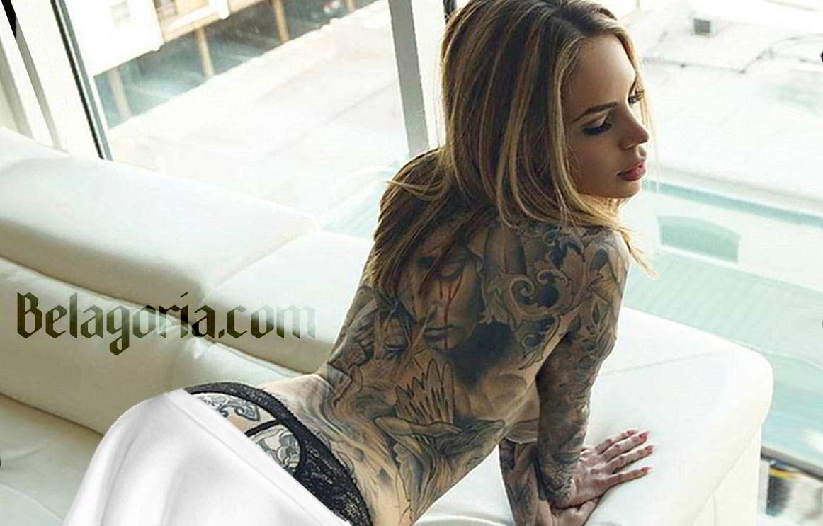 Una preciosa mujer rubia con tatuaje de la virgen en la espalda