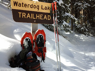 Exterior winter day at Waterdog Lakes trail head with red snowshoes and a day pack filled with snacks.