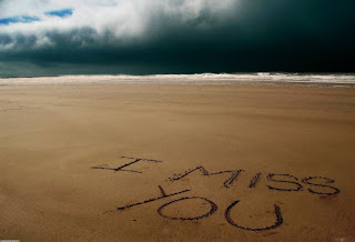 i miss you text written on beach sand