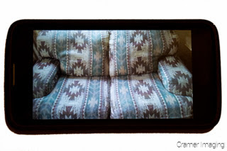 Cramer Imaging's photograph of a black smart phone displaying a patterned couch or furniture picture on the screen