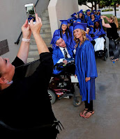 Photos of grads in line, someone taking a group shot with a cell phone