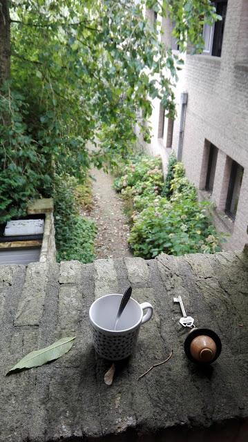 Kopje en kamersleutel op een muurtje van een dakterras van het klooster