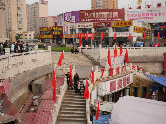 people removing Chinese and red flags at the Guomao Shopping Center in Mudanjiang