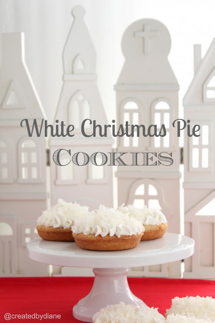 3 deep dish cookies on a white pedestal with a white ceramic Christmas village background