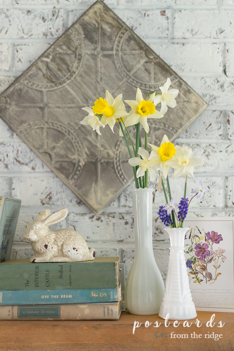 vintage milk glass with spring flowers and old books
