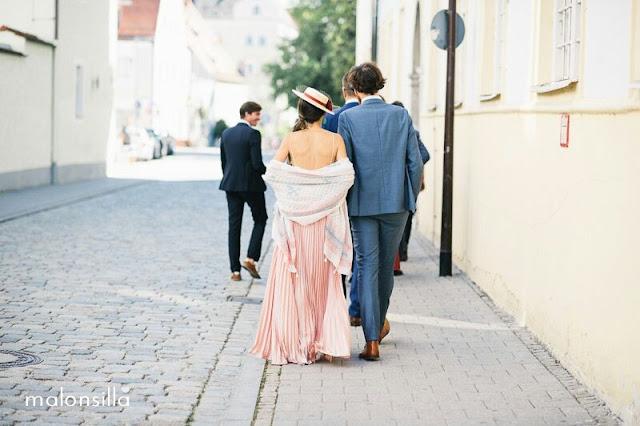 Invitada boda en Alemania con sombrero de flores y tapafeas en rosa y burdeos, falda plisada rosa palo, top con espalda descubierta de espaldas andando por la calle con peinado de coleta baja ladeada.