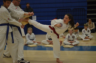 Childrens Taekwondo girl doing a side kick break