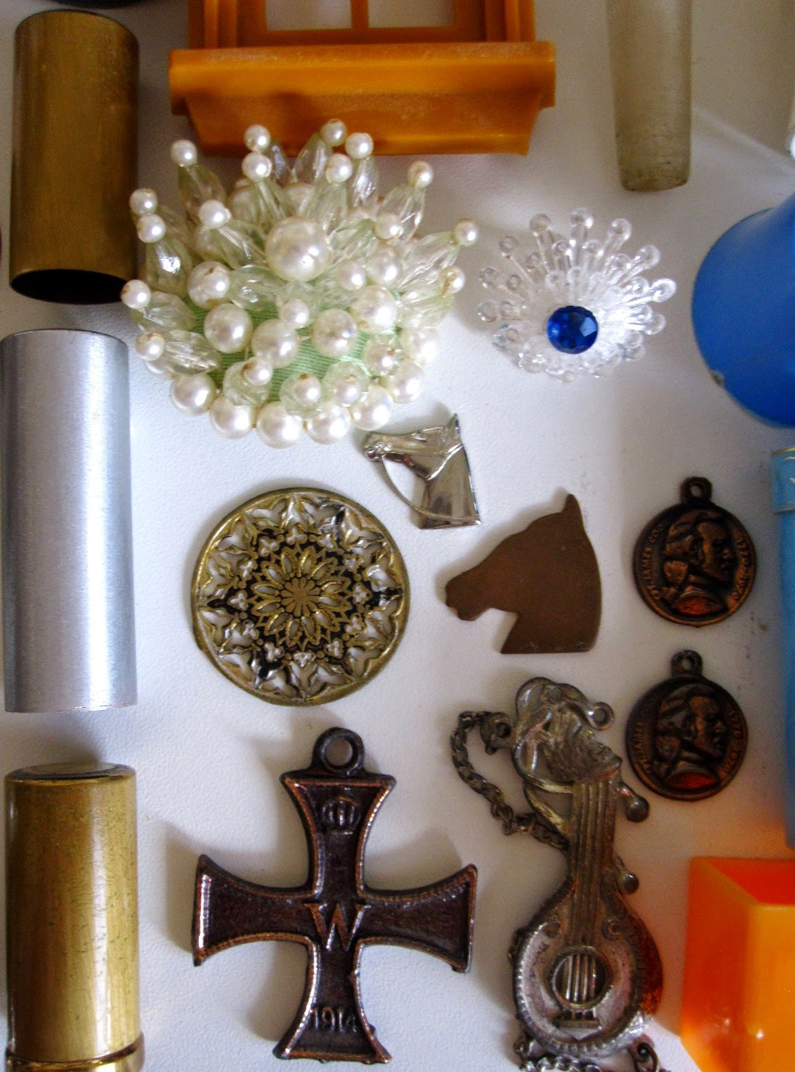 Three metal tubes, a selection of metal charms and two vintage brooches.