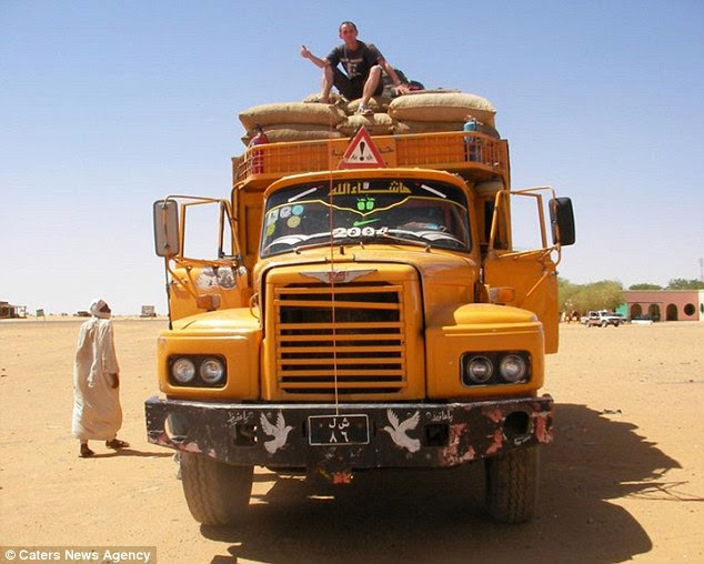 Mr Marie hitching a lift on a truck as part of his world travels. - A Big Thumbs Up. Traveller Hitchhikes 100,000 Miles Around The World Without Spending Any Money