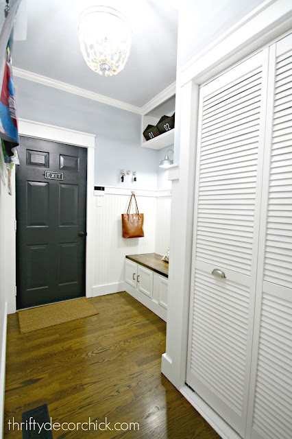 Classic white mud room with black door