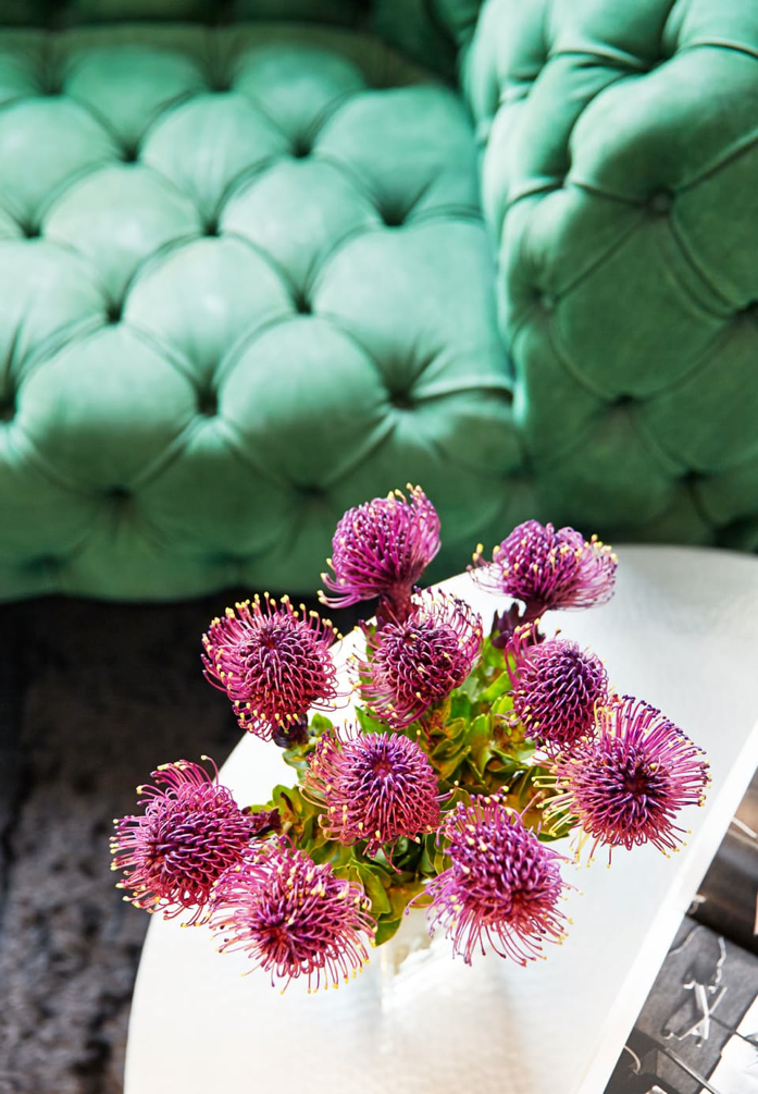 Place pretty pink flowers on your coffee table to enliven your space. Loving the pink and green color combo too.