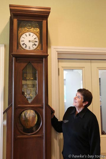 Kathy Smith, cellar door assistant. The Mission Winery and Restaurant, Taradale, Napier, with a grandfather clock that had stopped and only started today after an earthquake. photograph