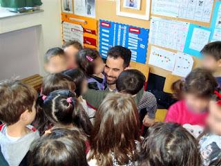 Ο Βαγγέλης περιτριγυρισμένος από παιδάκια που τον έχουν αγκαλιά