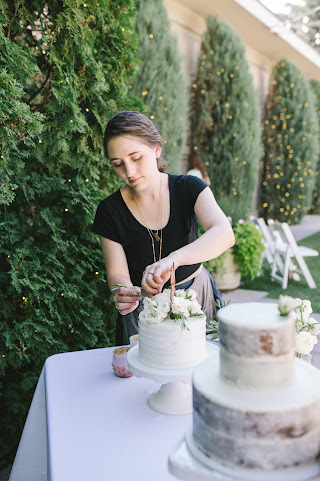 utah wedding florist placing lush white blooms, garden roses and herbs on a wedding cake