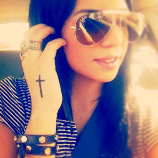Vemos a una chica e su auto con tatuaje de cruz en la mano