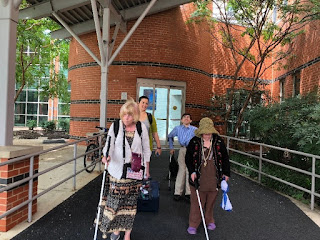 several participants arrive at the conference: 2 persons using canes, 1 person using crutches.