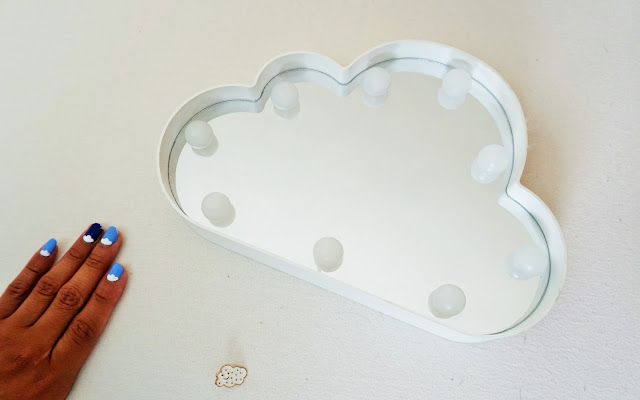 Flat lay of a plastic cloud mirror and cloud nail art design