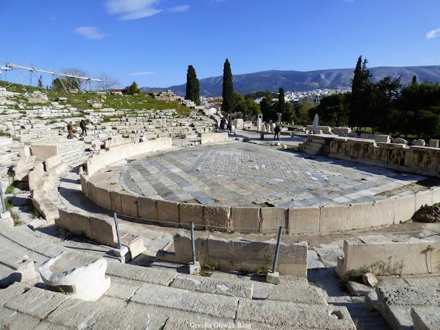 ruiny greckiego teatru boga Dionyzosa, marmurowe siedzenia w półkolistym ułożeniu, bezchmurne niebo w oddali cisy i cedry,  Akropol Ateny