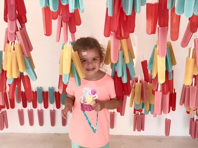 A toddler girl poses holding an ice cream cone in an art installation that has ice cream bars hanging from the ceiling