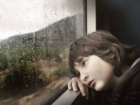 bored kid looking out the window when it's raining