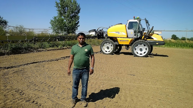 spray of agrochemical in guar gum seed cultivation farm in Europe for plant protection from insect , disease and weeds with a large machine