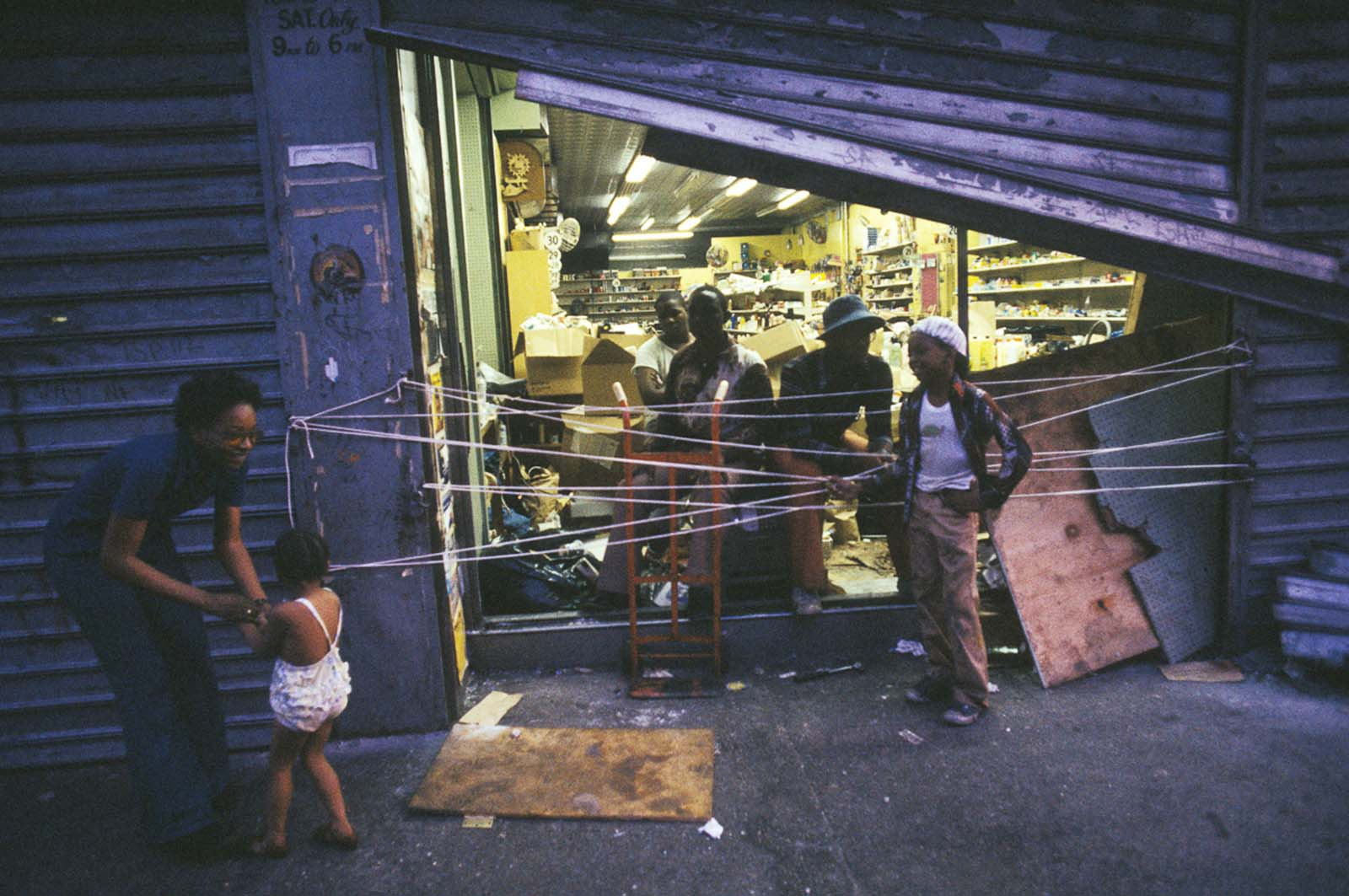 Store owners guard their damaged storefront against further looting.