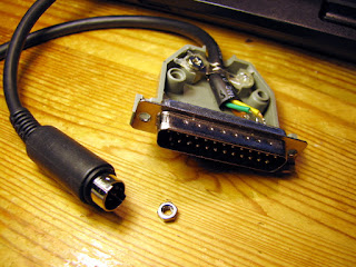 [Image: A cable with a  Mini-DIN connector on one end and a DB-25 connector on the other.]