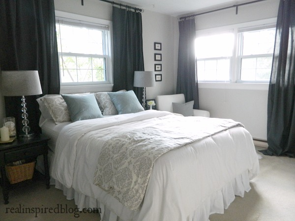 partridge gray master bedroom crystal lamps herringbone lampshades blue pillows white duvet bedding gray medallion duvet dark gray curtains beige carpet black tables nightstands