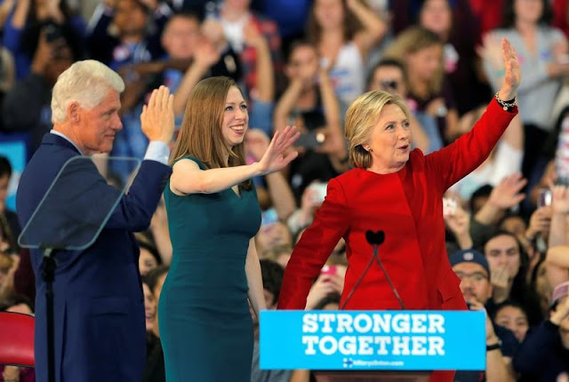 Image Attribute: Democratic presidential nominee Hillary Clinton along with her husband former President Bill Clinton and daughter Chelsea Clinton wave at a campaign rally in Raleigh, North Carolina November 8, 2016. REUTERS/Chris Keane