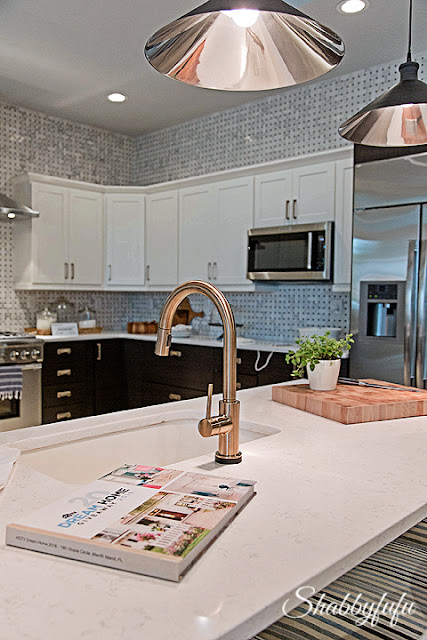 The kitchen of the HGTV Dream Home 2016. A grey and white backsplash compliments white and black cabinet fronts. Counter tops are a sleek white marble.