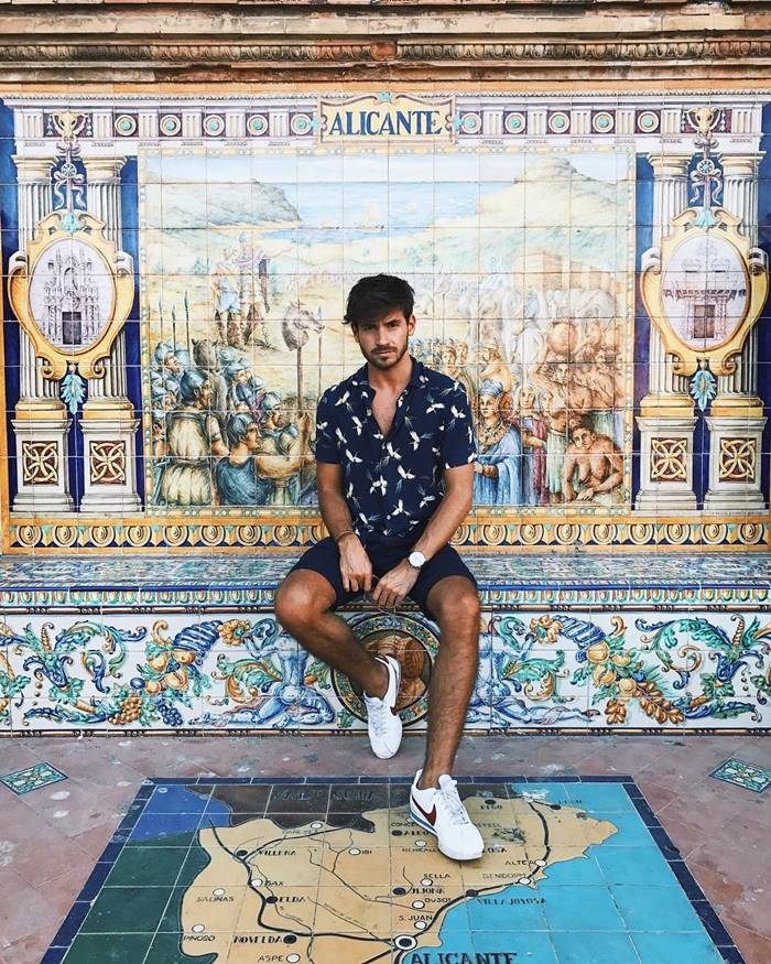 Look com camisa floral masculina nos tons de azul e shorts com tênis branco
