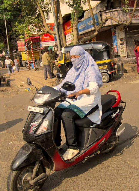 young woman wearing a scarf mask while riding a scooter in Pune
