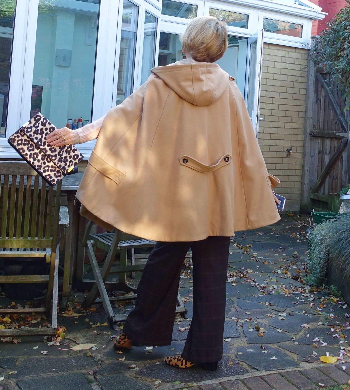 Rear view of a woman wearing a camel cape with leopard print accessories and original 1990s check trousers