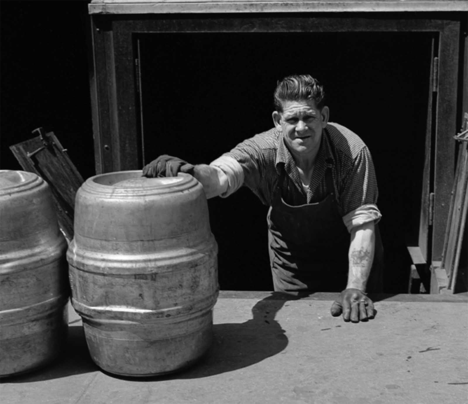 A man loads kegs of beer into a bar basement in 1953.