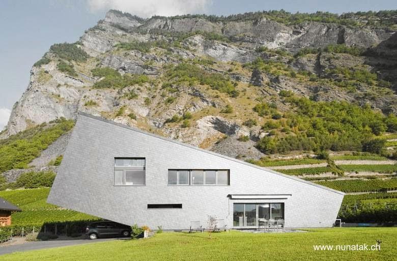 Fachada sur de casa contemporánea original en un valle de cultivos de vides en Suiza