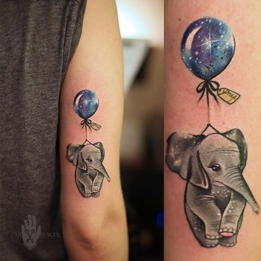Um elefante é ligado a um balão preenchido com um padrão cósmico neste obscuro da tatuagem.