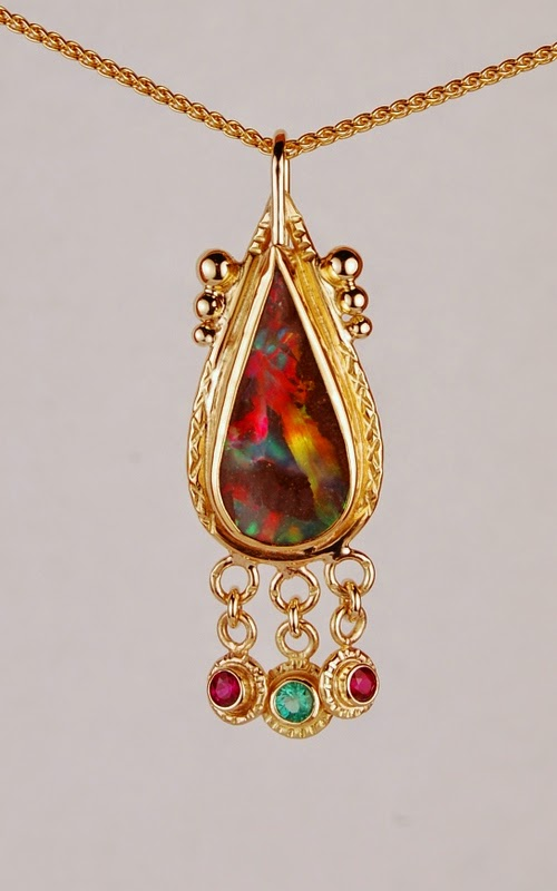 Pear shaped multicolor opal with dangling red and green stones