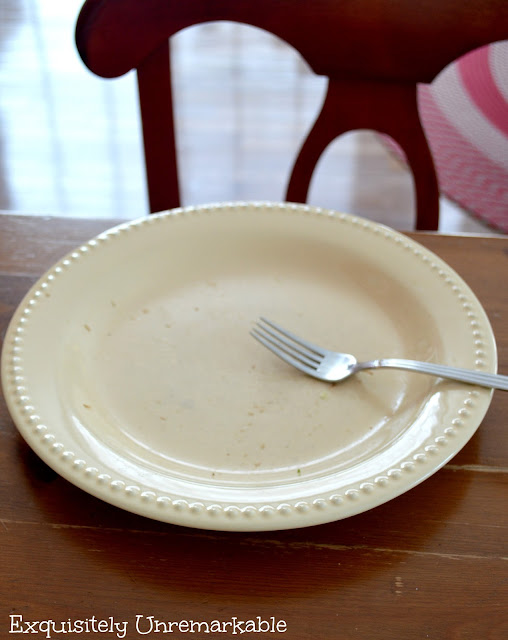 An empty yellow dinner plate and a fork on a wooden table