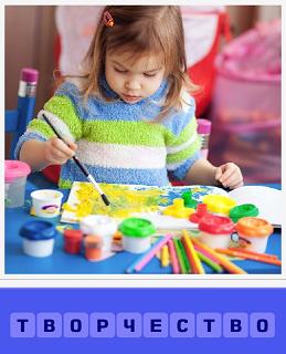 на столе ребенок занимается творчеством, рисует на бумаге