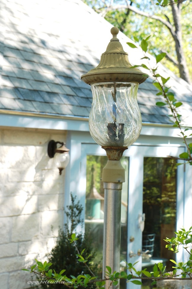garden shed after fresh paint with damaged outdoor lantern lamp on post