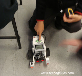 Child pressing button on EV3 robot