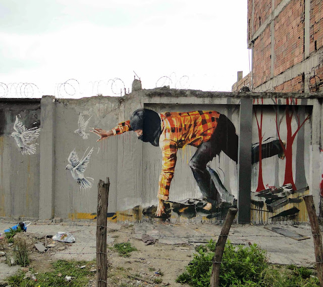 """Australian Street Artist Fintan Magee paints a new mural entitled """"Bad Hunter"""" on the streets of Bogota in Colombia. 1"""