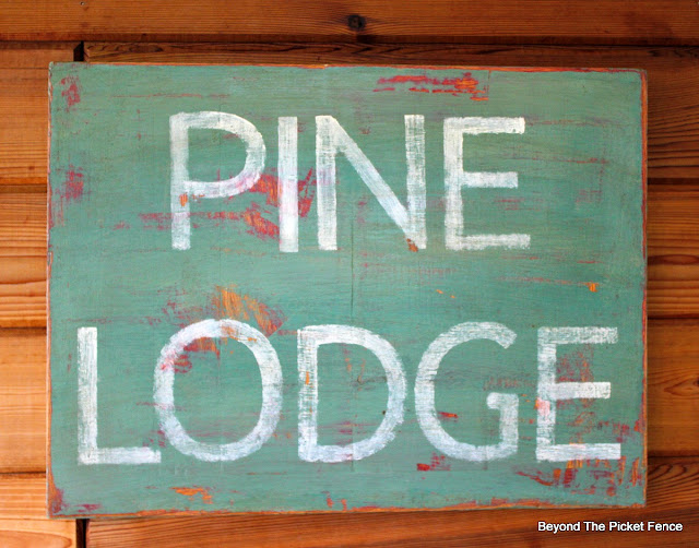 a cabin style rustic sign made from an old bread board