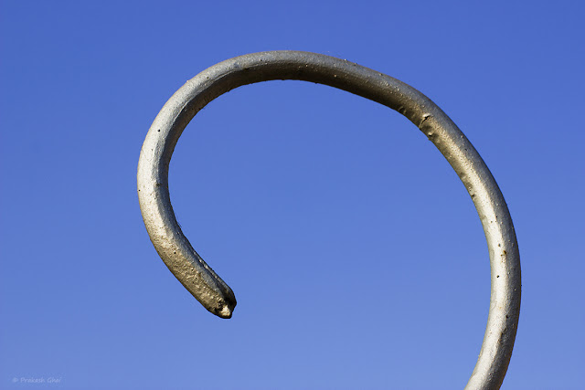 A Minimalist Photograph of Silver Metal Curl against Blue Sky.