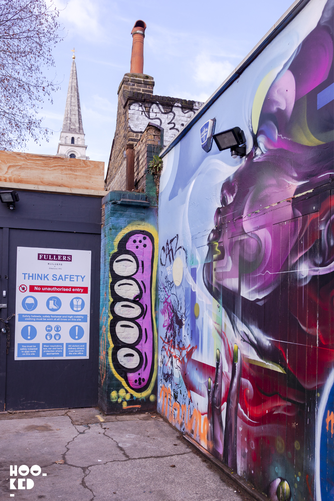 UK Street Artist Sweet Toofs' pink gummy teeth painted on a London wall