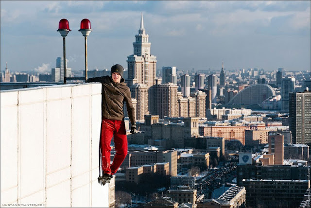 Man hanging from the building with Moscow skyline in the background