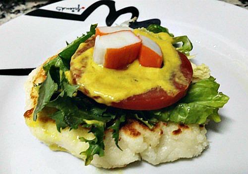 Una tostada de queso con tomate, lechuga y mostaza