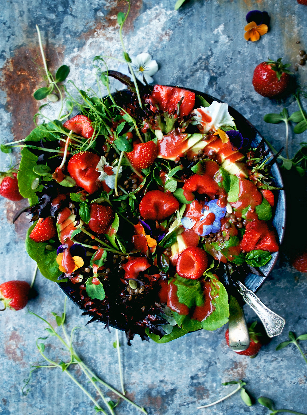 This vegan strawberry salad is packed with the best of the season - spring berries, the first greens, herbs, and flowers. It's spring in a bowl, with lentils and a pretty strawberry vinaigrette.
