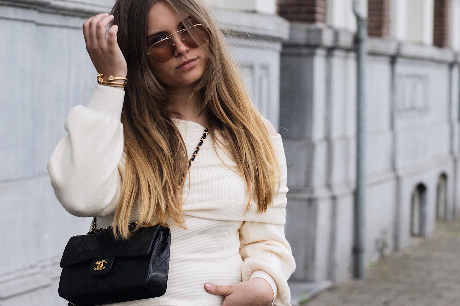 fashion blogger dominique candido wearing a zara top j brand jeans prada sunglasses chanel bag and celine sneakers