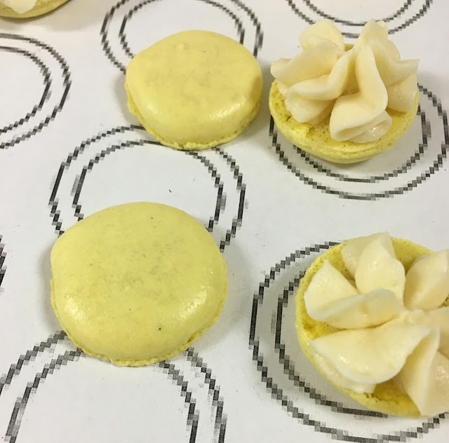 Lemon buttercream macarons sitting on a silicon macaron mat